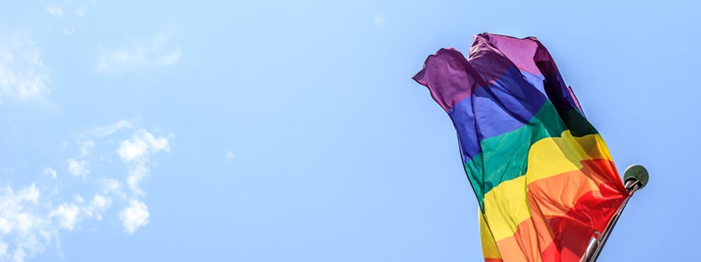 Pride (rainbow) flag in a blue sky