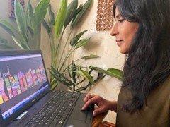 Artist Bushra Sultana looking at the Radical Kindness design on her laptop